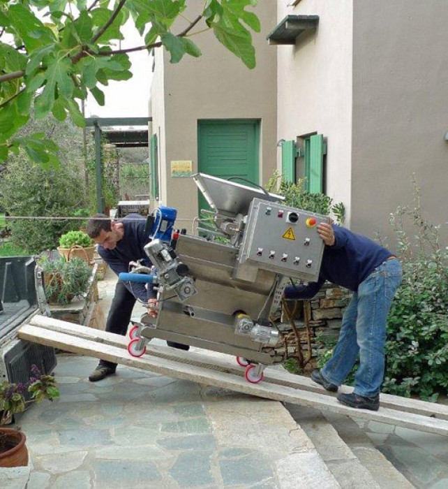 The olive press is carefully unloaded.